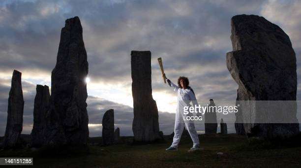 In this handout image provided by LOCOG Torchbearer 003 Kirsty Wade holds the Olympic Flame at the Calanais Standing Stones in Callanish as the sun...