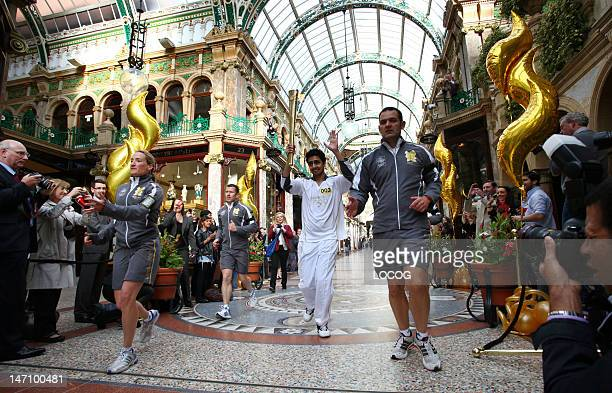 In this handout image provided by LOCOG Torchbearer 003 Yasser Ranjha carries the Olympic Flame through the County Arcade in Leeds city centre at the...