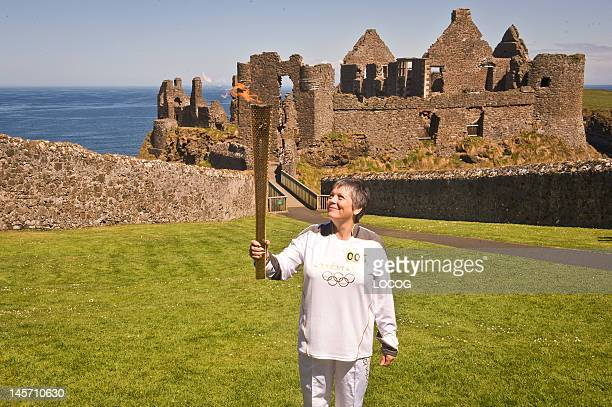 In this handout image provided by LOCOG Torchbearer 005 Jean Jones holds the Olympic Flame aloft in front of Dunluce Castle on day 17 of the London...