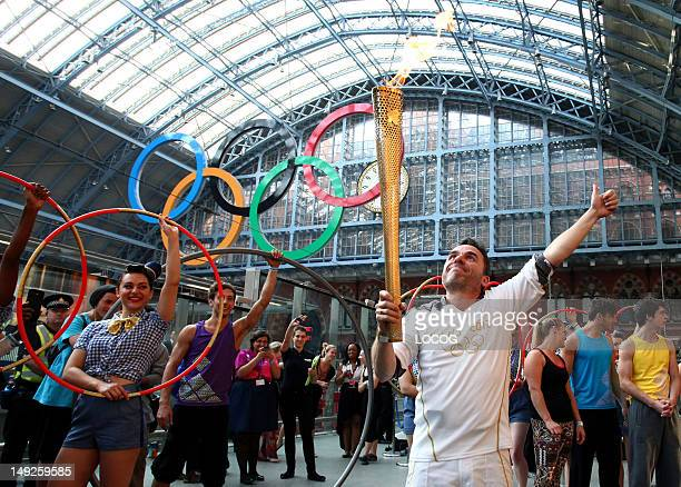 In this handout image provided by LOCOG Torchbearer 012 Daniel Mccubbin holds the Olympic Flame inside St Pancras International Railway Station...