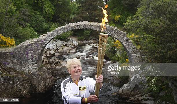 In this handout image provided by LOCOG Torchbearer 036 Katherine Milne holds the Olympic Flame next to the historic bridge of Carrbridge during the...