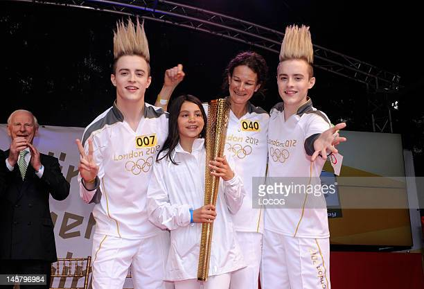 In this handout image provided by LOCOG Torchbearer 040 Sonia O'Sullivan poses for a photograph with Torchbearers 007 John and Edward Grimes aka...