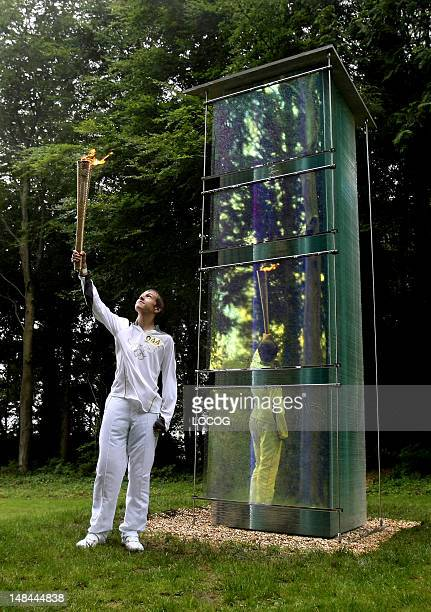 In this handout image provided by LOCOG Torchbearer 044 Ryan Hodd Jarvis holds the Olympic Flame at Cass Sculpture Park Goodwood Estate Hampshire...