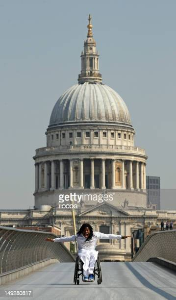 In this handout image provided by LOCOG Torchbearer 046 Ade Adepitan carries the Olympic Flame on the Millennium Bridge during Day 69 of the London...