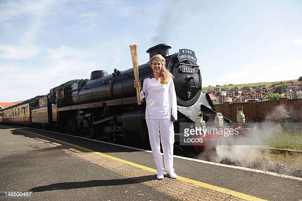 In this handout image provided by LOCOG Torchbearer 049 Kelly Williams stands in front of the steam locomotive Sir Nigel Gresley holding the Olympic...