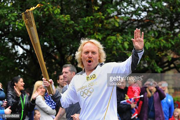 In this handout image provided by LOCOG Torchbearer 050 Keith Lemon carries the Olympic Flame on the Torch Relay leg through Stockport on Day 37 of...