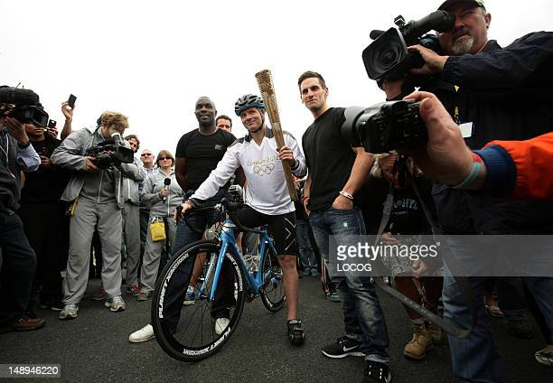 In this handout image provided by LOCOG Torchbearer 056 Craig Preece holds the Olympic Flame on the race track of Brands Hatch with former athlete...