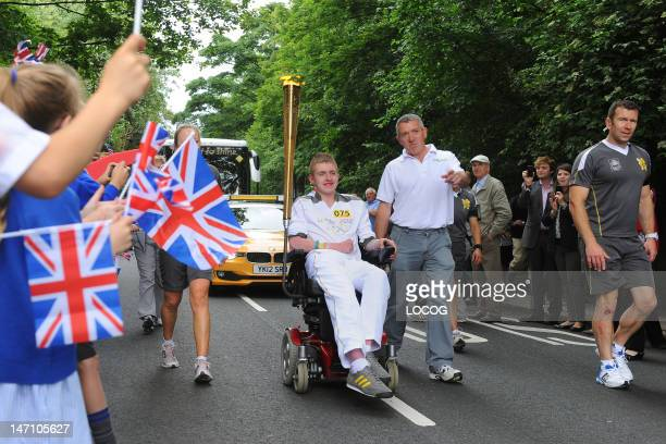 In this handout image provided by LOCOG Torchbearer 075 Jack Mitchell is cheered on by local children waving Union Jack flags as he carries the...