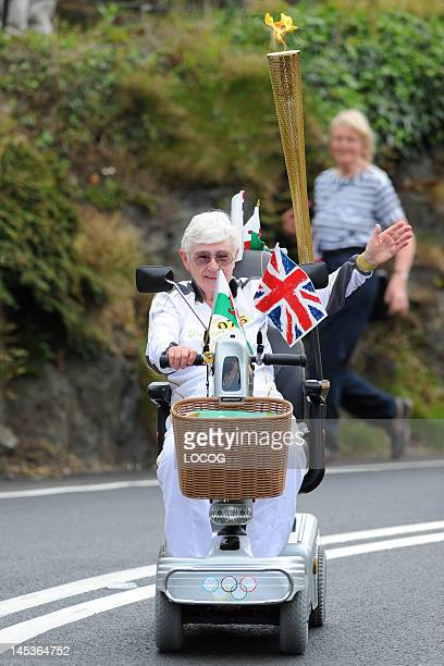 In this handout image provided by LOCOG Torchbearer 075 Jill Edge carries the Olympic flame on the leg between Fishguard and Newport on May 27 2012...