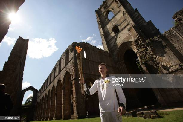 In this handout image provided by LOCOG Torchbearer 085 Lewis Birkinshaw holds the Olympic Flame in front of Fountains Abbey on the Torch Relay leg...