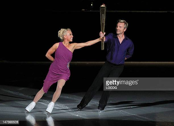 In this handout image provided by LOCOG Torchbearer 100 Jayne Christensen and Torchbearer 107 Christopher Dean carry the Olympic Flame in the...