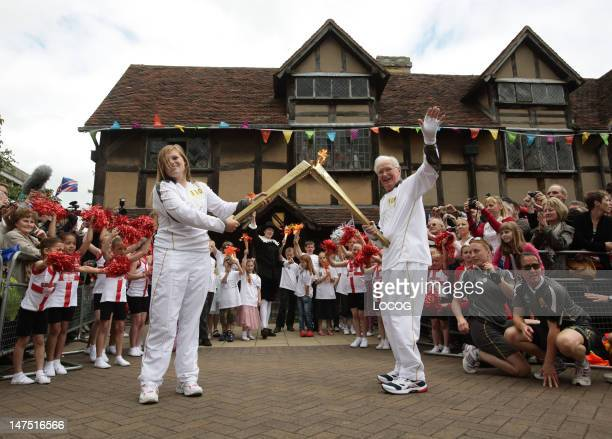 In this handout image provided by LOCOG Torchbearer 109 Peter Wyatt passes the Olympic Flame to Torchbearer 110 Camilla Hadland outside Shakespeare's...