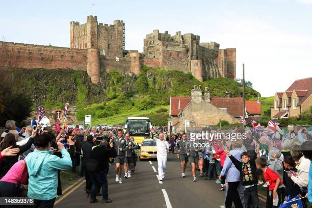 In this handout image provided by LOCOG Torchbearer 122 Brian Tinnion carries the Olympic Flame in front of Bamburgh Castle on the Torch Relay leg...
