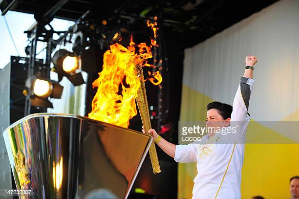 In this handout image provided by LOCOG Torchbearer 137 Jules Hanks of Sleaford uses the Olympic Flame to light the cauldron on stage at the...