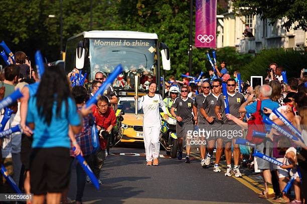 In this handout image provided by LOCOG Torchbearer 147 Li Na carries the Olympic Flame on the Torch Relay leg between the London Borough of Enfield...