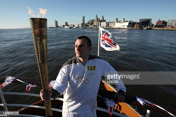 In this handout image provided by LOCOG Torchbearer 157 Craig Lundberg carries the Olympic Flame across the River mersey between Birkenhead and...