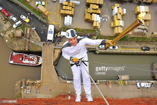 In this handout image provided by LOCOG Torchbearer Alan Ellinson holds the Torch before he abseils with the Olympic Flame down the side of the Royal...