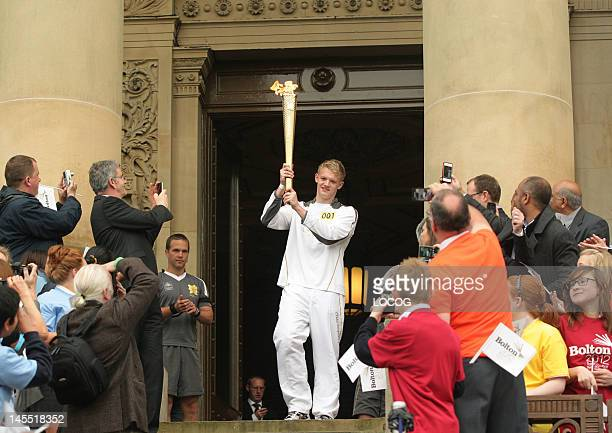 In this handout image provided by LOCOG Torchbearer Antony Evitts holds the Olympic Flame outside Bolton Town Hall in Victoria Square as the Flame...