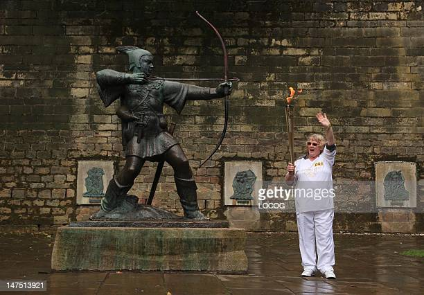 In this handout image provided by LOCOG Torchbearer Barbara Green poses with the Robin Hood statue before she carries the Olympic Flame on the Torch...