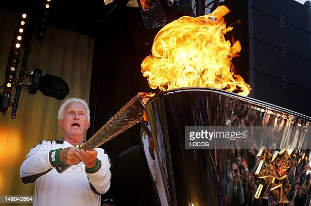 In this handout image provided by LOCOG Torchbearer David Cole lights the cauldron with the the Olympic Flame during the Torch Relay leg through...