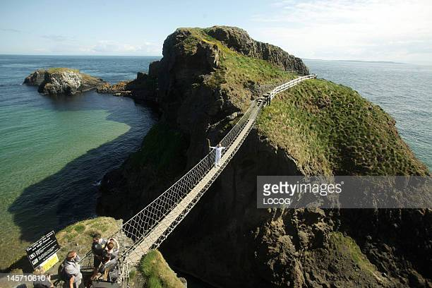In this handout image provided by LOCOG Torchbearer Denis Broderick holds the Olympic Flame on the CarrickaRede rope bridge which links the mainland...