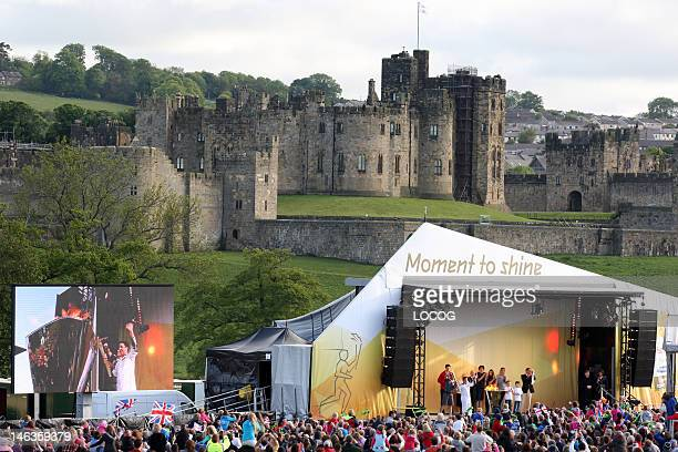 In this handout image provided by LOCOG Torchbearer Lewis Denny lights the cauldron in front of Alnwick Castle which was used in the Harry Potter...