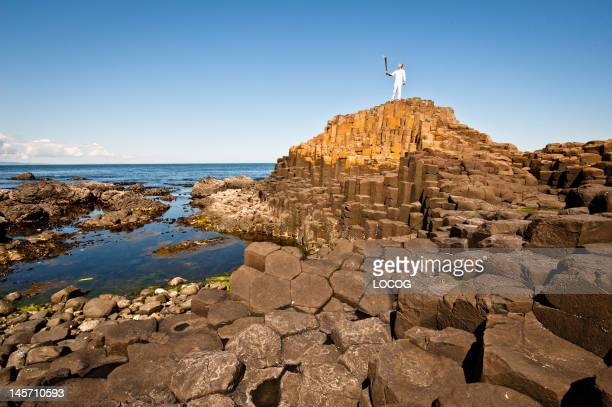 In this handout image provided by LOCOG Torchbearer Peter Jack holds the Olympic Flame aloft on the Giant's Causeway County Antrim on day 17 of the...