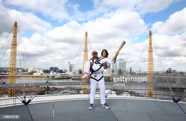 In this handout image provided by LOCOG Torchbearers John Amaechi and Nadia Comaneci pose with the Olympic Torch on the viewing platform of the North...