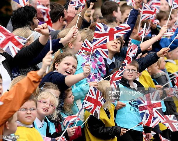 In this handout image provided by LOCOG Young schoolchildren wave Union Jack flags as they cheer on the Torch Relay in Long Sutton during Day 47 of...