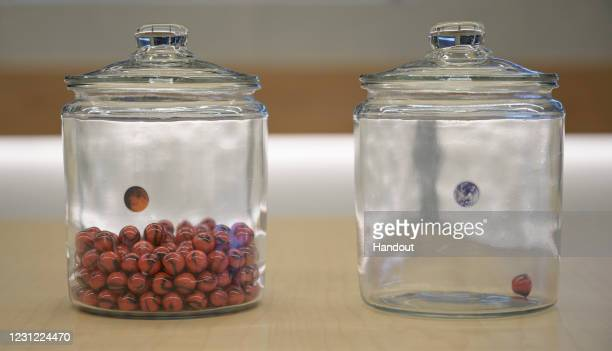 In this handout image provided by NASA,, A jar with an Earth sticker and one marble inside and a jar with a Mars sticker full of marbles are seen on...