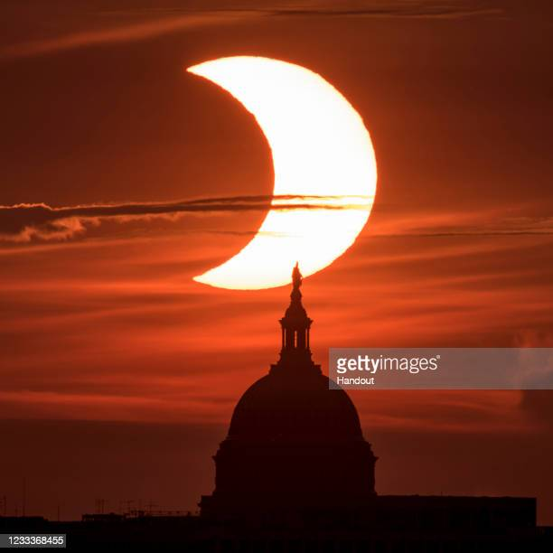 In this handout image provided by NASA, a partial solar eclipse is seen as the sun rises behind the Capitol Building on June 10, 2021 in Arlington,...