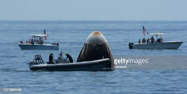 In this handout image provided by NASA a recovery support team and recreational boaters surround the SpaceX's Crew Dragon capsule spacecraft with...
