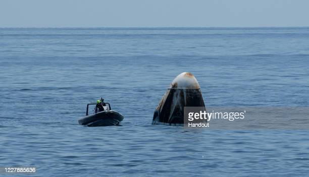 In this handout image provided by NASA, a recovery support team flanks the SpaceX's Crew Dragon capsule spacecraft, with NASA astronauts Robert...