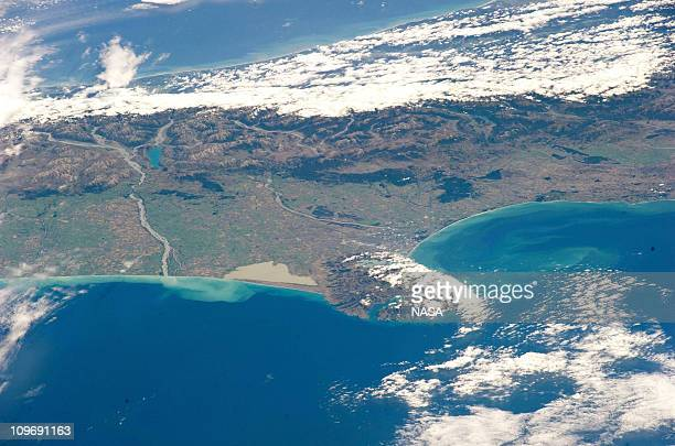 In this handout image provided by NASA a view across the South Island of New Zealand one can see the Southern Alps mountain range along the length of...