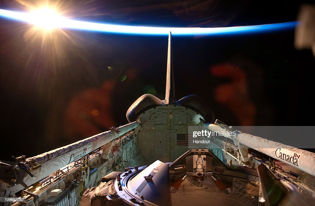 In this handout image provided by NASA, an orbital sunrise brightens this view of space shuttle Discovery's vertical stabilizer, orbital maneuvering system (OMS) pods, docking mechanism, remote manipulator system/orbiter boom sensor system (RMS/OBSS) and payload bay during flight day 12 activities March 7, 2011 in Space. Discovery, on its 39th and final flight, is carrying the Italian-built Permanent Multipurpose Module (PMM), Express Logistics Carrier 4 (ELC4) and Robonaut 2, the first humanoid robot in space to the International Space Station. Discovery was in service for 27 years and will be decommissioned and sent to a museum. Two remaining shuttle missions are planned before the program ends.