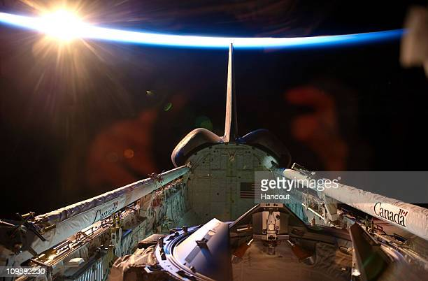 In this handout image provided by NASA an orbital sunrise brightens this view of space shuttle Discovery's vertical stabilizer orbital maneuvering...
