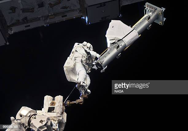 In this handout image provided by NASA anchored to a Canadarm2 mobile foot restraint NASA astronaut Garrett Reisman STS132 mission specialist...
