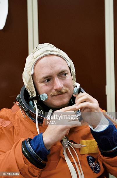 In this handout image provided by NASA astronaut Mark E Kelly STS108 pilot dons a training version of the fullpressure launch and entry suit prior to...