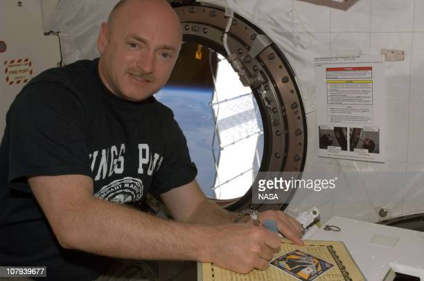 In this handout image provided by NASA, astronaut Mark E. Kelly, STS-124 commander, makes an entry in the International Space Station ship's log in...