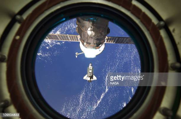 In this handout image provided by NASA backdropped by a blue and white part of Earth space shuttle Discovery approaches the International Space...