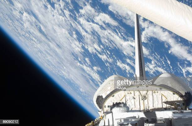 In this handout image provided by NASA, backdropped by a blue and white Earth and the blackness of space, a partial view of Space Shuttle Endeavour's...