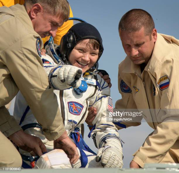 In this handout image provided by NASA Expedition 59 NASA astronaut Anne McClain is helped out of the Soyuz MS11 spacecraft just minutes after she...