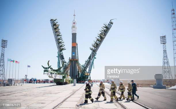 In this handout image provided by NASA, Firefighters walk past the Soyuz rocket as the service structure arms are closed around it, at Baikonur...
