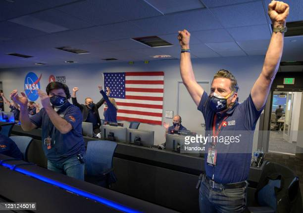 In this handout image provided by NASA, members of NASA's Perseverance rover team react in mission control after receiving confirmation the...