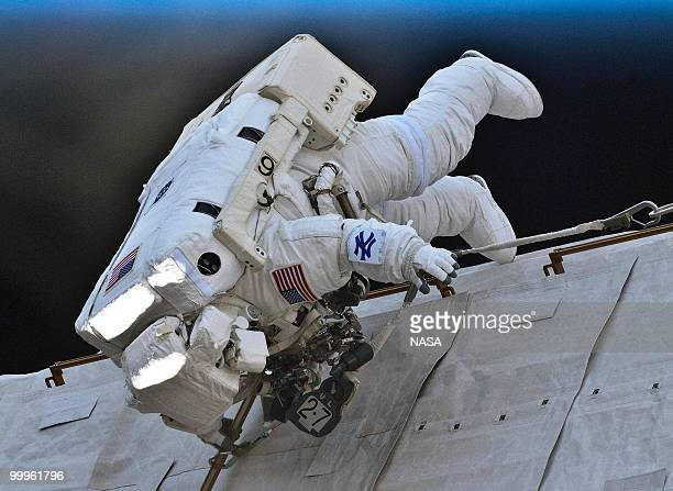 In this handout image provided by NASA NASA astronaut Garrett Reisman STS132 mission specialist wears a New York Yankee symbol on his instruction...