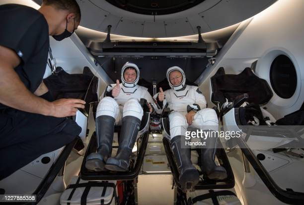 In this handout image provided by NASA, NASA astronauts Robert Behnken and Douglas Hurley are seen inside the SpaceX Crew Dragon capsule spacecraft...