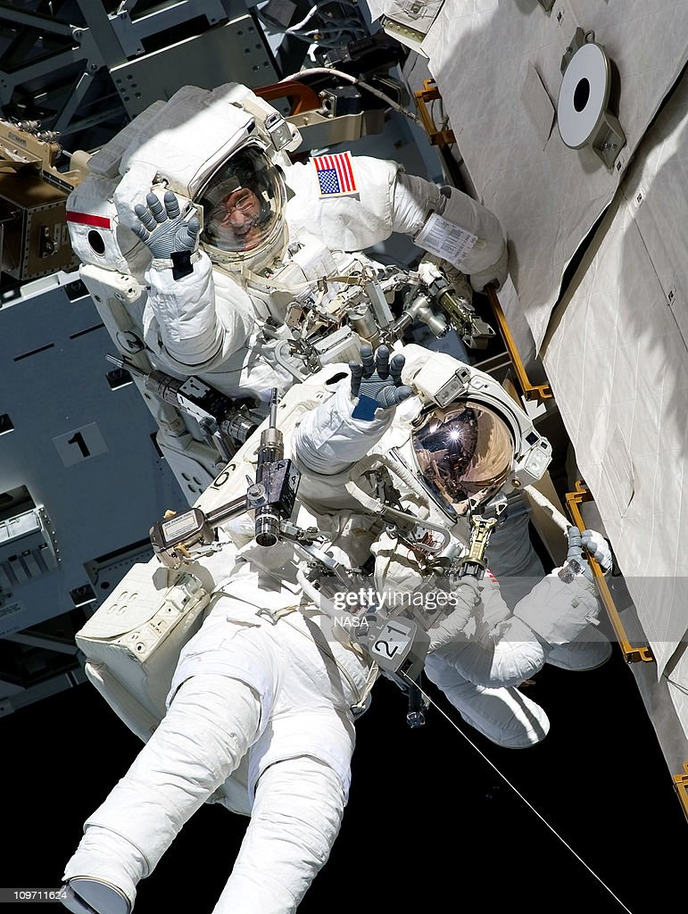 In this handout image provided by NASA, NASA astronauts Steve Bowen and Alvin Drew, both STS-133 mission specialists, wave as they participate in the mission's first session of extravehicular activity (EVA) as construction and maintenance continue on the International Space Station February 28, 2011 in Space. During the six-hour, 34-minute spacewalk, Bowen and Drew installed the J612 power extension cable, move a failed ammonia pump module to the External Stowage Platform 2 on the Quest Airlock for return to Earth at a later date, installed a camera wedge on the right hand truss segment, installed extensions to the mobile transporter rail and exposed the Japanese 'Message in a Bottle' experiment to space. Discovery, on its 39th and final flight, is carrying the Italian-built Permanent Multipurpose Module (PMM), Express Logistics Carrier 4 (ELC4) and Robonaut 2, the first humanoid robot in space to the International Space Station.