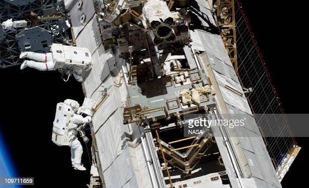 In this handout image provided by NASA, NASA astronauts Steve Bowen and Alvin Drew, both STS-133 mission specialists, participate in the mission's...