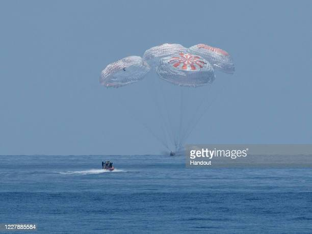 In this handout image provided by NASA, SpaceX's Crew Dragon capsule spacecraft, with NASA astronauts Robert Behnken and Douglas Hurley onboard,...