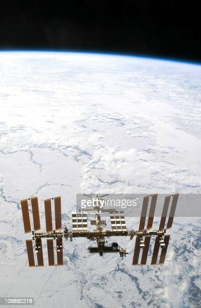 In this handout image provided by NASA, the International Space Station is seen from the space shuttle Discovery as the two orbital spacecraft...